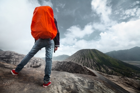 rock climb: Backpacker standing on an edge of volcano crater and looking to another volcano  Stock Photo
