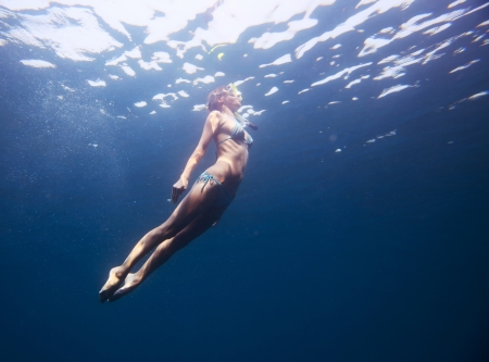 fining: Young woman diving on a breath hold in a tropical sea