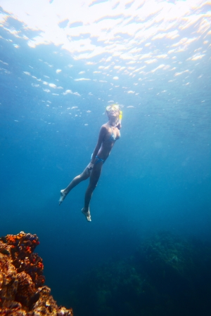 Young woman diving on a breath hold in a tropical sea photo
