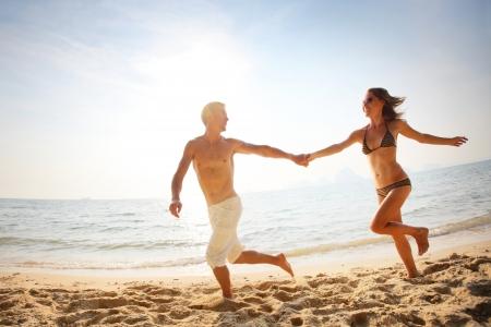 uomo felice: Giovane coppia felice in esecuzione insieme tra una spiaggia al giorno pieno di sole