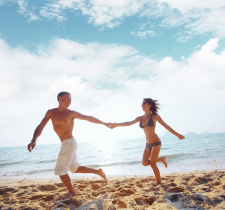 among: Young happy couple running together among a beach at sunny day Stock Photo