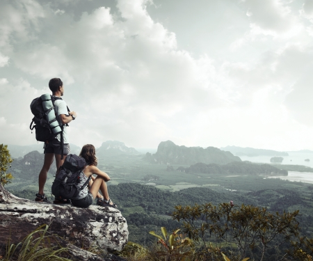 Hikers with backpacks enjoying valley view from top of a mountain Stock Photo - 16840924