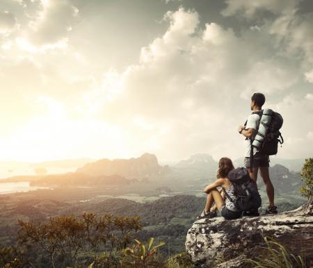 climbing: Los excursionistas con mochilas disfrutar de vistas al valle desde la cima de una monta�a Foto de archivo