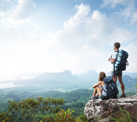 rock climbing: Hikers with backpacks enjoying valley view from top of a mountain