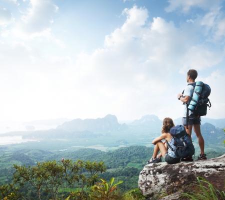 escalando: Los excursionistas con mochilas disfrutar de vistas al valle desde la cima de una monta�a Foto de archivo