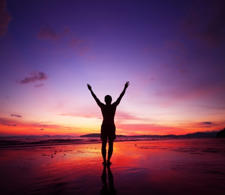 Young man standing on tropical beach with raised hands at sunset photo