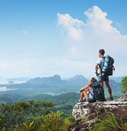 woman hiking: Young backpackers relaxing on top of a mountain and enjoying a valley view