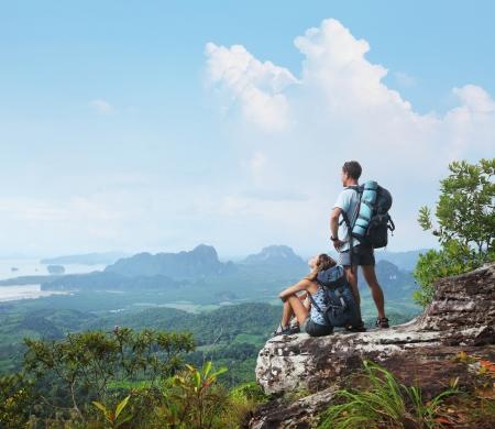 aventura: Mochileros jóvenes de relax en la cima de una montaña y disfrutar de una vista del valle