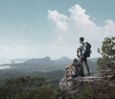 Young backpackers relaxing on top of a mountain and enjoying a valley view Stock Photo - 16840789