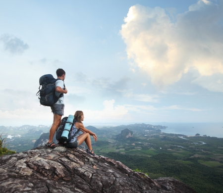 team journey: Hikers with backpacks enjoying valley view from top of a mountain