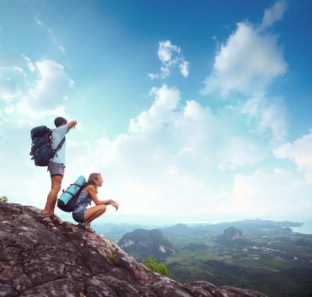 valley view: Giovani turisti con zaini gode vista sulla valle dalla cima di una montagna Archivio Fotografico