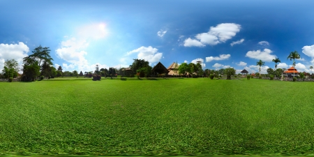 equirectangular: Panorama of a meadow with green grass blue sky with clouds and buildings among trees. Equirectangular panorama 360 degrees Stock Photo