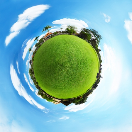 Spherical panorama of a green meadow with trees and buildings and blue sky with clouds photo