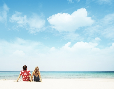 man looking at sky: Young couple sitting on white sand by sea and looking to a blue clear sky