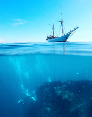 Sail boat in a tropical calm sea on a surface and divers underwater exploring a shipwreck photo
