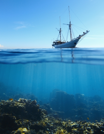 Sail boat in tropical calm sea and coral reef underwater