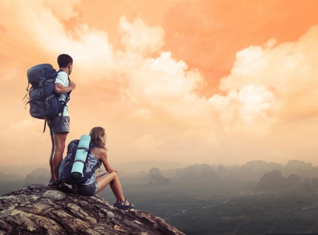 Two hikers with backpacks standing on top of a mountain and enjoying a valley view photo