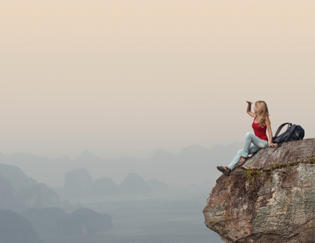 Young woman with backpack sitting on a cliff and enjoying a sunset photo