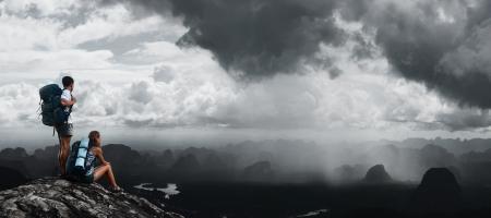 Men and women in the rain: Hai người đi bộ với ba lô đứng trên đỉnh của một ngọn núi và tìm đến một thung lũng ngập lụt do mưa nhiệt đới