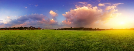 horizon over land: Green wide meadow with grass and colorfull cloudy sky at sunset