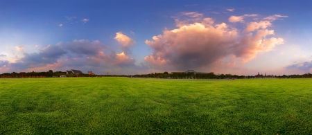 Green wide meadow with grass and colorfull cloudy sky at sunset Stock Photo - 16875497