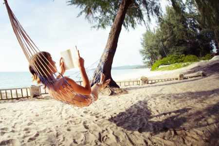 Young woman reading a book lying in a hammock on tropical sandy beach Stock Photo - 16881468