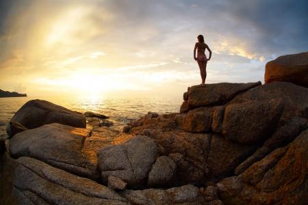 mujer mirando el horizonte: Mujer de pie sobre una roca y mirando hacia el horizonte sobre el mar Foto de archivo