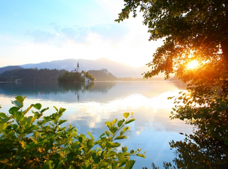 bled: Calm Bled lake at sunrise with clouds in a sky