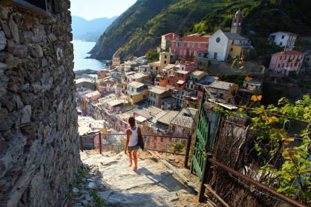 Young waman walking on stairs of small street of Vernazza town. Italy photo