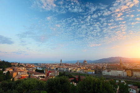 Florence city with green trees on the foreground with fluffy clouds in a sky at sunrise photo