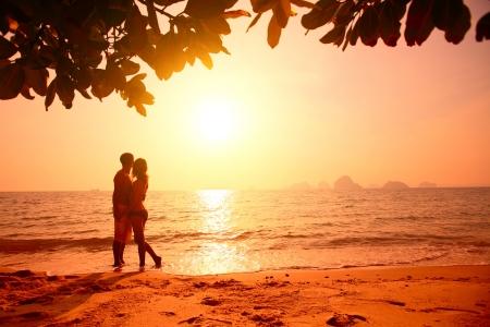 Imagen en tonos rojos de una pareja en una playa tropical al atardecer