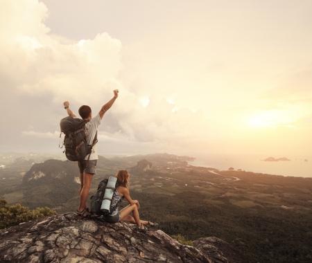 valley view: Due escursionisti con zaini in piedi sulla cima di una montagna con grande vista sulla valle