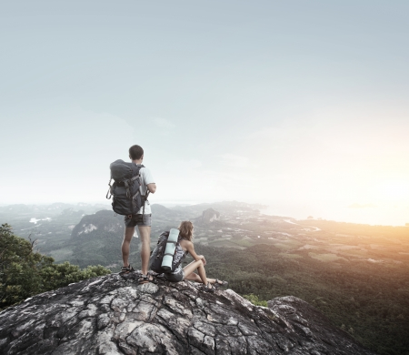 Hikers with backpacks standing on top of a mountain and enjoying a valley view photo