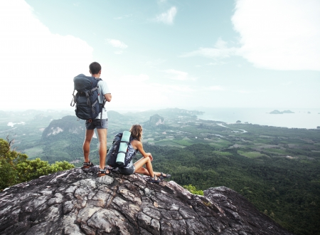 Hikers with backpacks standing on top of a mountain and enjoying a valley view Stock Photo - 16881738