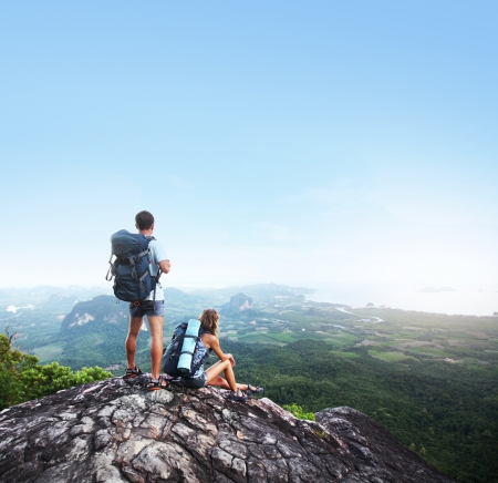 Hikers with backpacks standing on top of a mountain and enjoying a valley view Stock Photo