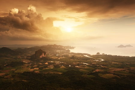 ao: Stormy tropical clouds over valley with town forests and limestone mountains Stock Photo