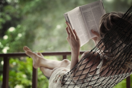 read: Woman lying in a hammock in a garden and enjoying a book reading