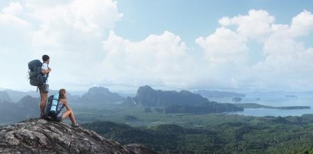 valley view: Due turisti con zaini rilassante sulla cima di una montagna e godere vista sulla valle