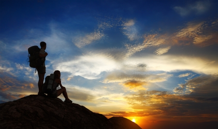 climbing sport: Silhouettes of two tourists with backpacks relaxing on top of a mountain and enjoying sunset view