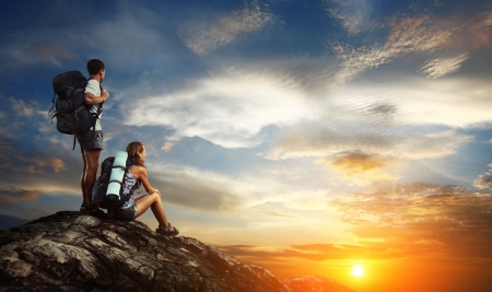 trek: Two tourists with backpacks relaxing on top of a mountain and enjoying sunset view