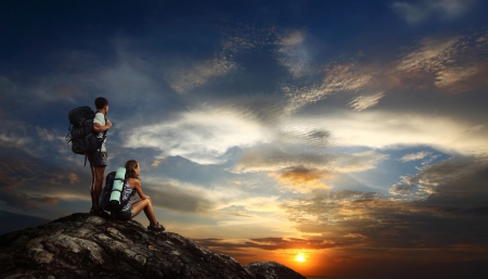 Two tourists with backpacks relaxing on top of a mountain and enjoying sunset view Stock Photo - 18043079