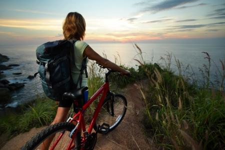Travel Backpack: Rider femenina con mochila que se coloca en la cima de una colina con su bicicleta de monta�a y disfrutar de la puesta de sol del mar