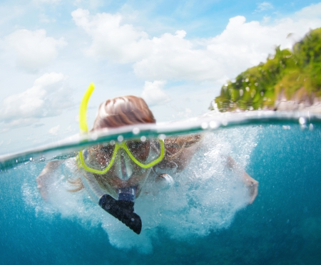beneath the surface: Underwater portrait of a woman snorkeling in tropical sea. Splitted image with sky and green island in frame.