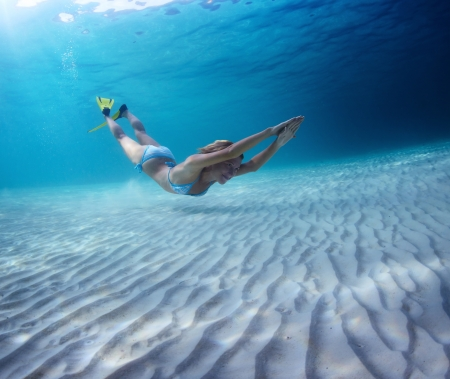 Underwater full length portrait of a woman having fun in a tropical sea over sandy bottom Stock Photo - 18043052