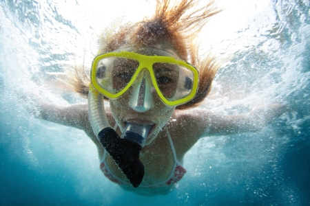 Close up underwater portrait of a woman making skin dive with a lot of bubbles on face photo