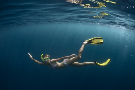 profound: Underwater shoot of a young lady diving on a breath hold in a clear profound sea with sunbeams shining through the water