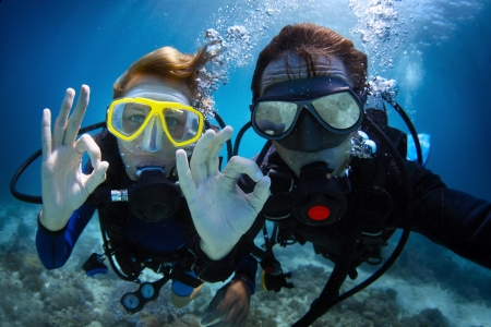 buddy: Underwater shoot of a young couple diving with scuba in a tropical sea and showing ok signal