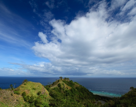 apo: Green hills on tropical island situated in the midst of sea. Apo island, Philippines Stock Photo