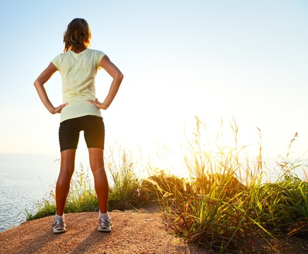 freedom leisure activity: Young slim lady worn traning clothes standing on countryside path and enjoying sunset