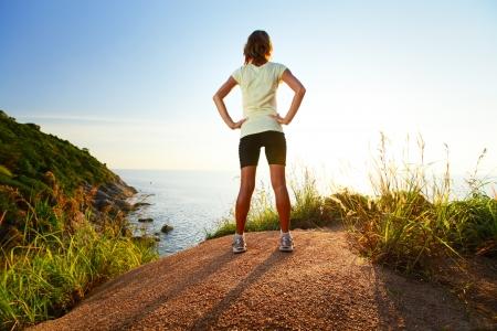 mujer mirando el horizonte: Señora joven delgado usado ropa Traning de pie en la cima de una colina y disfrutar de la puesta del sol